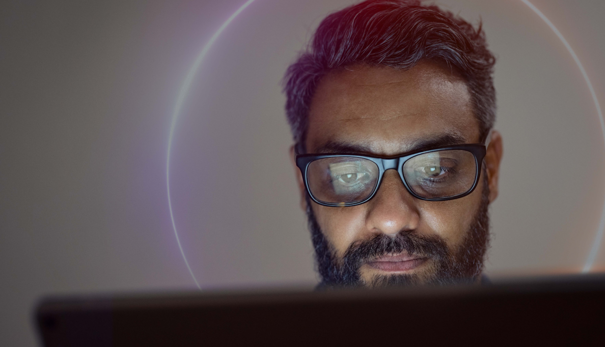 Man working on laptop with beam of light behind him