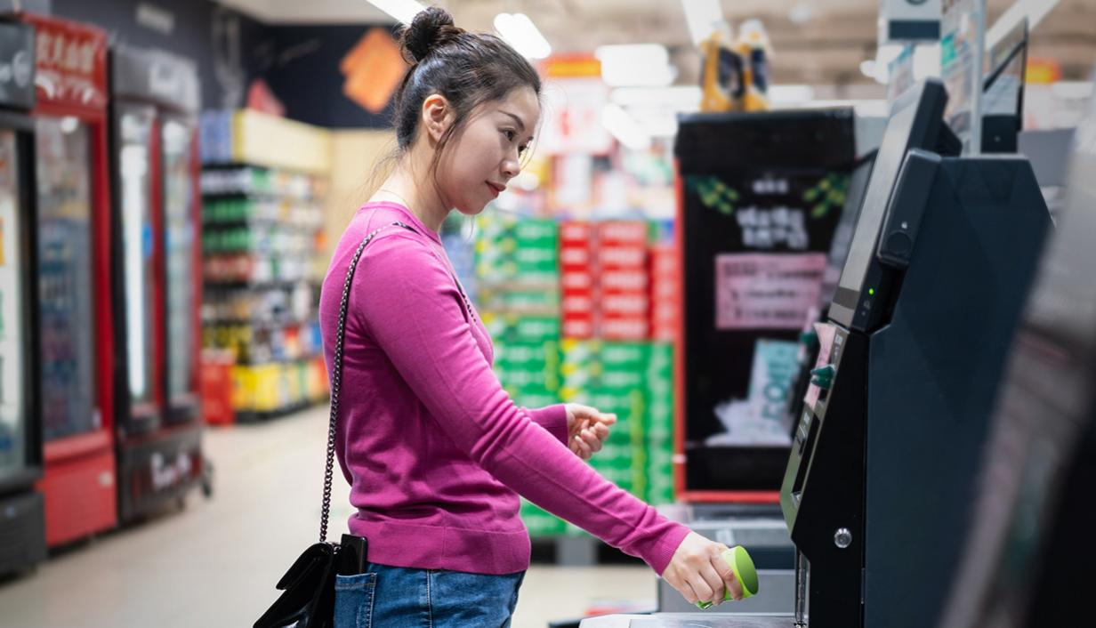 Woman at grocery store self check-out.