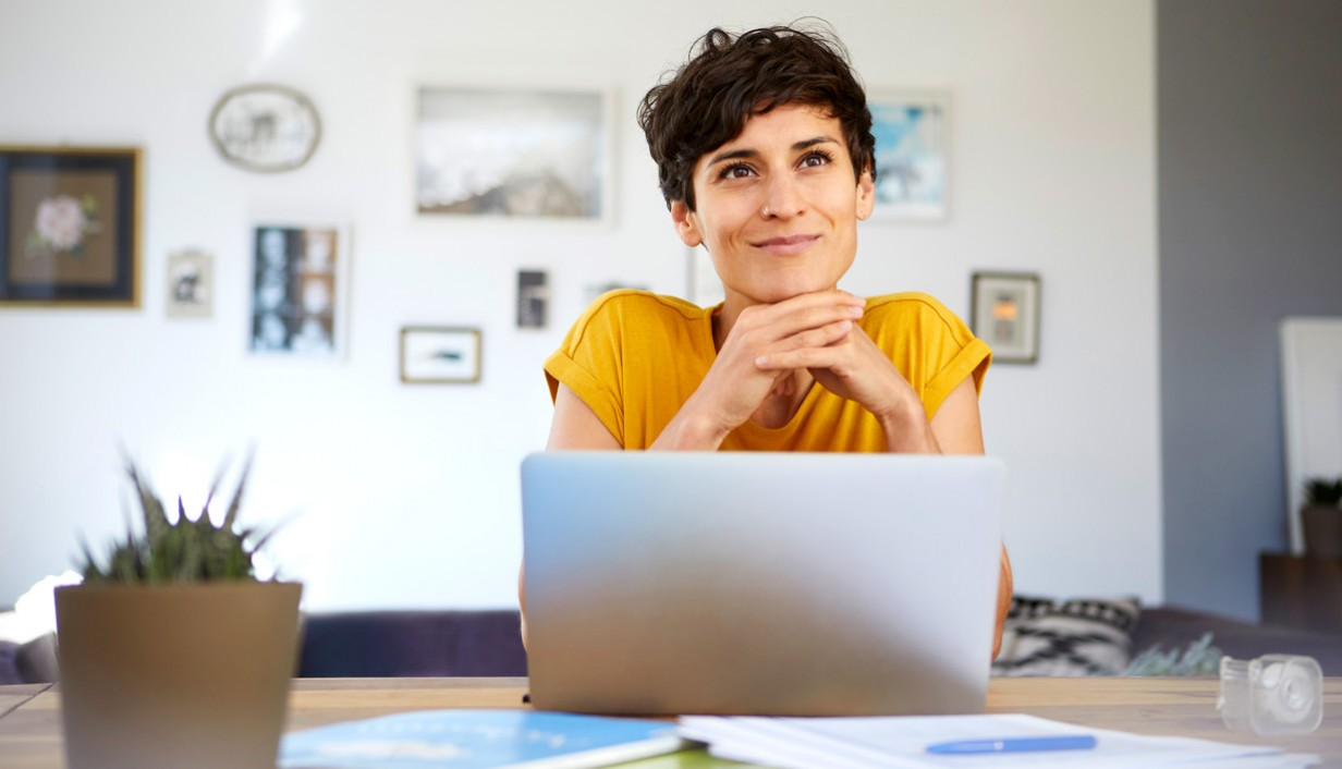 woman in yellow shirt in front of laptop computer