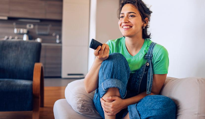 Women on sofa with remote in hand, watching TV