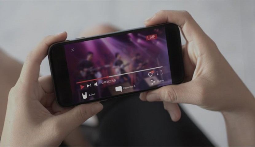A woman streams a concert on her smartphone.